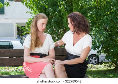 Two Women Dressed in Formal Clothing Having Serious Heartfelt Conversation Together While Sitting on Park Bench on Sunny Summer Day