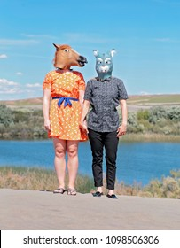 two women dressed in GENERIC latex animal masks holding hands in the sand