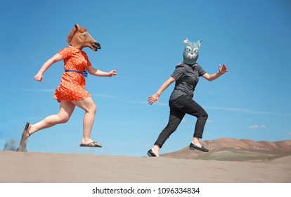 two women dressed in latex animal masks running in the sand