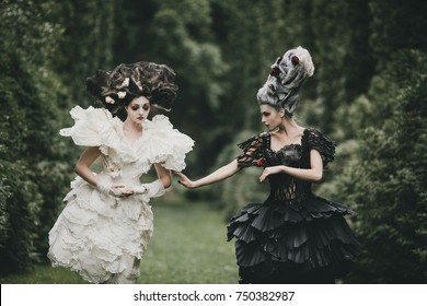 Two women dresses like heroes from 'Alice in Wonderland' pose in a green park