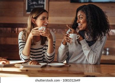 Two women drinking coffee and smiling at each other pointing towards milk mustache in coffee shop. Friends sitting at a cafe with coffee and snacks on the table.