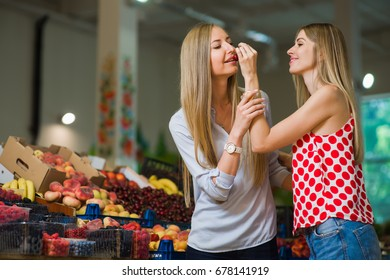 Two women eat cherry at food market. Fruits and berries on background. A women is smiling.