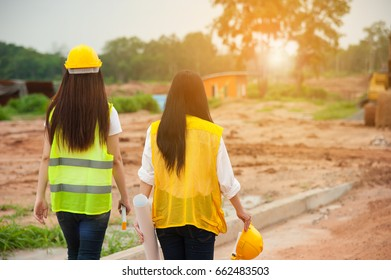 Two women engineers with blueprint walking in a construction site