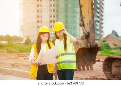 Two women engineers looking blueprint in a construction site