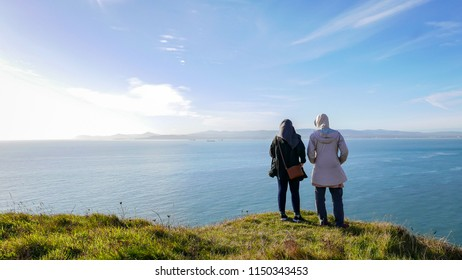 Two women are enjoying the beautiful scenery of Howth in Dublin from a steep cliff.