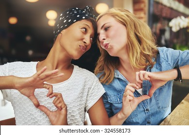 Two women ethnic friends kissing each other for fun