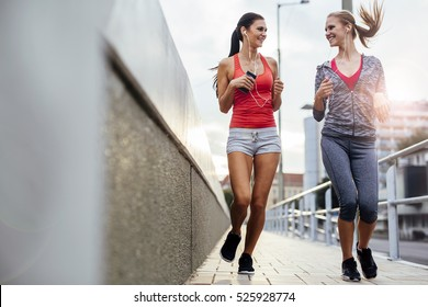 Two women exercising by jogging in the city while sun is setting
