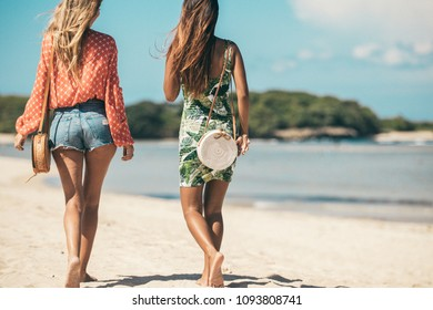 Two Women with fashionable stylish rattan bag and silk scarf outside. Tropical island of Bali, Indonesia. Rattan handbag and silk scarf.