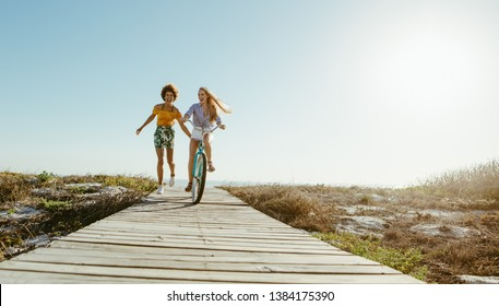 Two women friends with a bicycle on the seaside boardwalk. Woman riding the bike with her friends holding from the back and running.