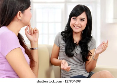 Two women friends chatting on the couch at home