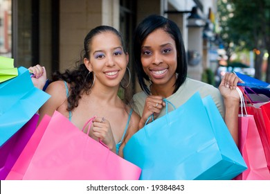 Two women friends in the city on a shopping trip carrying colorful shopping bags.