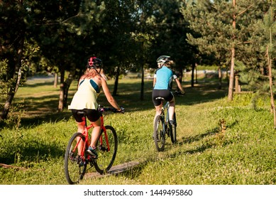 Two women friends riding bikes offroad at the forest
