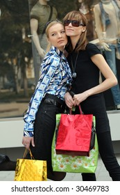 two women friends with shopping bags