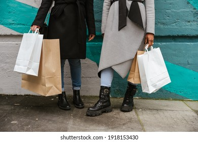 Two women friends are shopping together in the city - Unrecognizable portrait of shopping bags in hands on a green wall