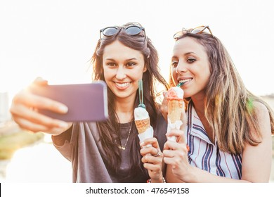 Two women friends take selfie while eating ice cream near river at sunset in summer