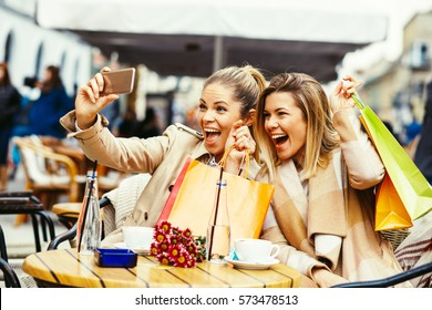 Two women friends taking a selfie in cafe after shopping