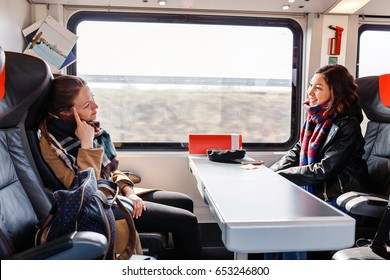 Two women Friends talk and laugh while traveling by train