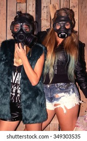 Two women in front of a wooden wall with gasmasks.