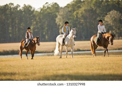 Two women and a girl horseriding in a field