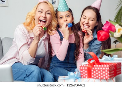 Two women and girl together at home celebrating birthday sitting on sofa wearing festive caps holding party blowers laughing cheerful - Shutterstock ID 1126904402