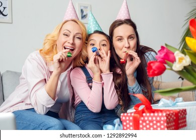 Two women and girl together at home celebrating birthday sitting on sofa wearing festive caps looking camera blowing at party horns smiling joyful - Shutterstock ID 1292892994