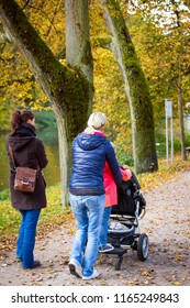 two women and girl walking with a buggy through the park