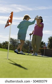 Two women giving high-five on golf course