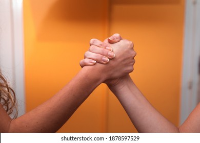 Two women greeting clashing their hands