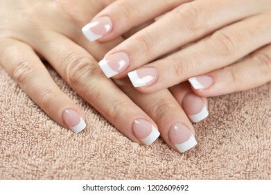 Two women hands with french manicure. Close-up. View from above. Background-terry towel beige.
