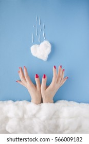 Two women hands with red nails, catching a falling heart, in a heavenly scenery with the heart and the clouds made of cotton-wool, on a blue sky paper background.