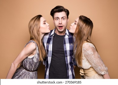 Two women and an handsome guy, Love triangle. Two young women kissing to the man.