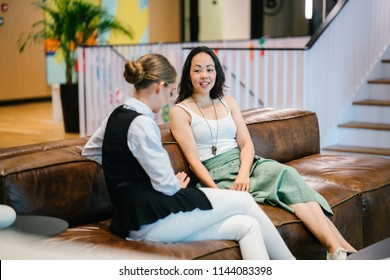 Two women have a business meeting on a couch in an office. One is a Caucasian woman and the other Asian Chinese. They are professionally dressed and having an intense discussion.