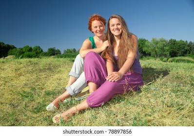 Two women have fun on top of hill in park