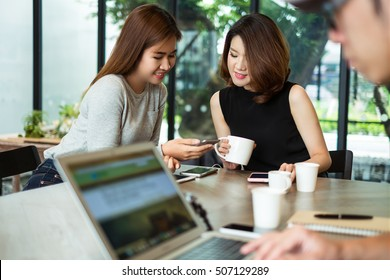 Two women having fun at the cafe and looking at smart phone. Woman showing something to her friends sitting.