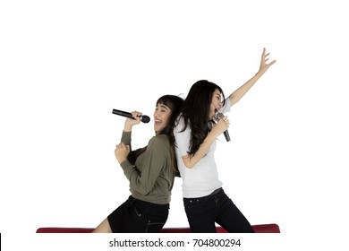 Two women having fun together while singing karaoke, isolated on white background