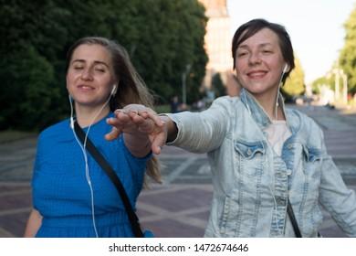 Two women in headphones dancing in the street