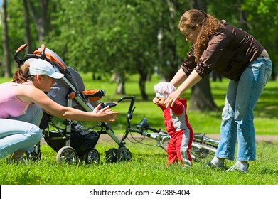 Two women help toddler to do first steps in the park. Green grass and foliage around they. It`s a summer. Baby carriage and bike are here too.