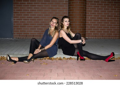 two women in high heels sitting in the night on a curb