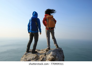 two women hikers looking at the view on seaside mountain top rock edge