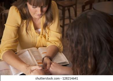 Zwei Frauen halten Hände und beten, während sie die Bibel studieren.
