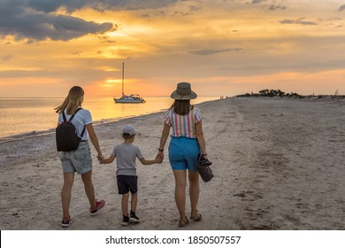 Two women hold the hands of a son. Family holidays on the sea coast. Unconventional family. Equality right, lesbian, homosexuality lifestyle, lgbt. Friends are walking on the beach .