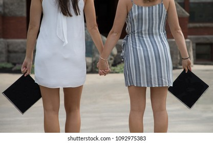 Two women are holding hands to celebrate friendship on graduation day
