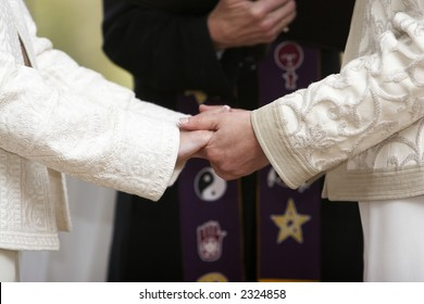 Two women holding hands during a wedding celebration