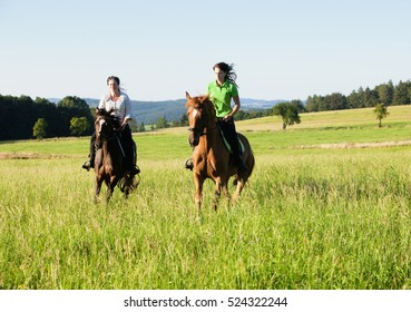 Two Women Horseback Riding in a Landscape