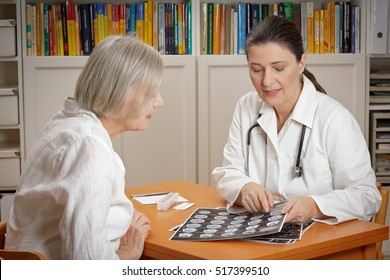 Two women in a hospital office: middle aged doctor in white coat showing her senior patient a printed sheet of computer tomography images of her brain