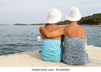 Two women hugging on sea shore, sunny beach, wearing hand knitted white hats