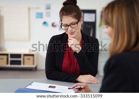 two women in a job interview sitting at the desk looking at a curriculum vitae