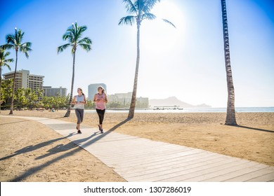 Two Women jogging on the beach boardwalk between two palm trees. Women working out on a gorgeous beach boardwalk while on vacation