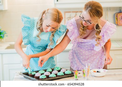 two women in the kitchen preparing food.