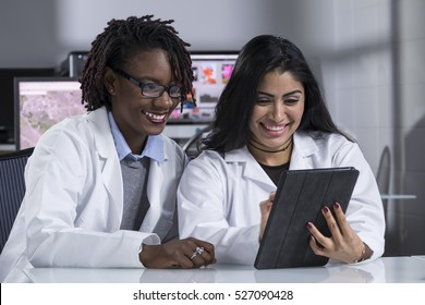 Two women in lab coats looking at an ipad computer